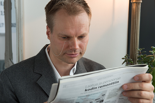 a man reading news paper with reading glasses